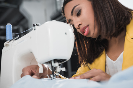 Foto de african american seamstress working with sewing machine - Imagen libre de derechos