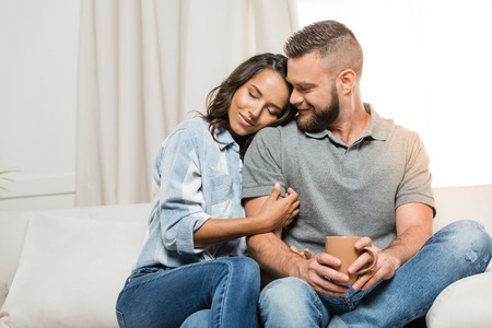Photo pour tender couple with closed eyes hugging on sofa at home - image libre de droit