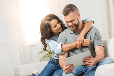 Foto de happy couple with digital tablet hugging on sofa at home - Imagen libre de derechos