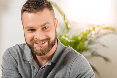 Photo pour Close-up portrait of handsome bearded man smiling at looking away - image libre de droit