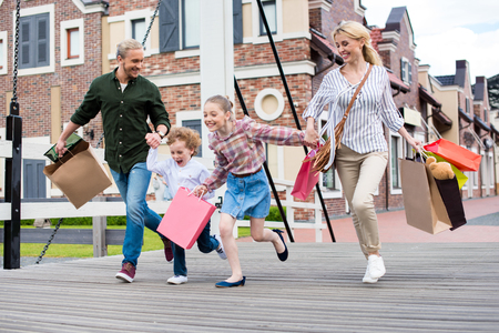 Photo pour family holding hands and running with shopping bags on the bridge - image libre de droit