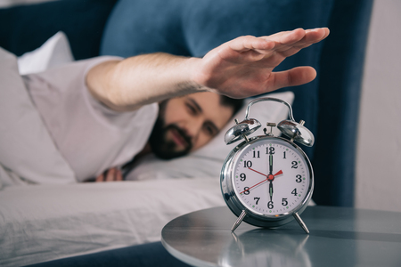 Photo pour young man trying to turn off alarm clock while lying in bed at morning - image libre de droit