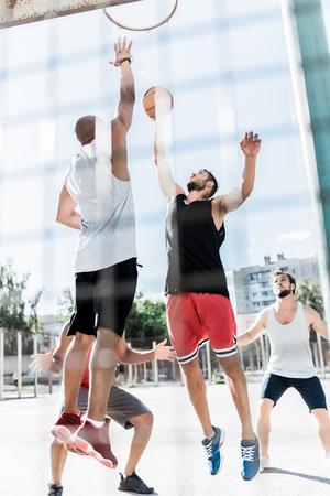 Photo pour athletic men playing basketball together on court - image libre de droit