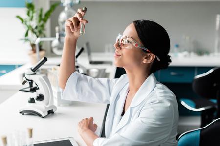 Foto de young chemist in protective glasses and white coat examining test tube in lab - Imagen libre de derechos