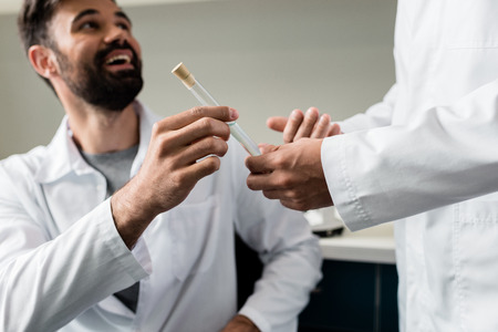 Foto de chemists in lab coats holding test tube with reagent together - Imagen libre de derechos