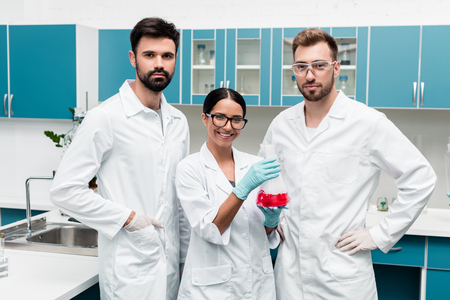 Foto de young scientists in white coats holding flask with reagent and smiling at camera in chemical lab - Imagen libre de derechos