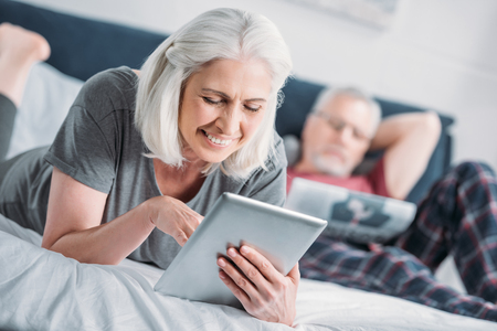 Photo for smiling senior woman using tablet while resting on bed - Royalty Free Image