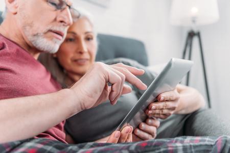 Foto de couple with digital tablet resting in bed together - Imagen libre de derechos