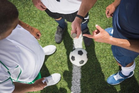 Photo pour referee holding coin before start of soccer match on pitch - image libre de droit