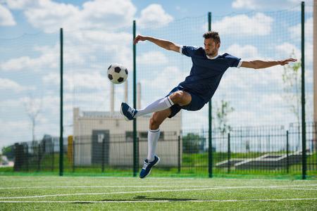 Photo pour soccer player kicking ball on soccer pitch - image libre de droit