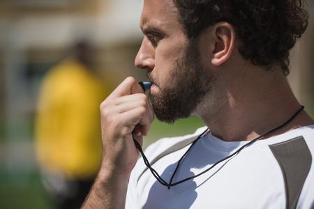Foto de soccer referee whistling in whistle on soccer pitch during game - Imagen libre de derechos