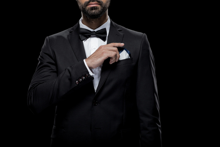 Photo pour cropped view of businessman in bow tie and tuxedo with napkin, - image libre de droit