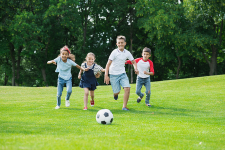 Foto de happy multiethnic kids playing soccer with ball in park - Imagen libre de derechos