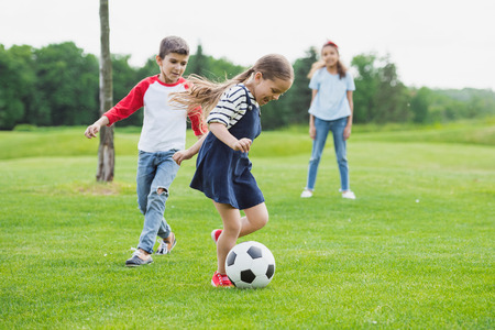 Foto de cheerful children playing soccer with ball on green grass - Imagen libre de derechos