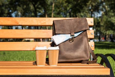 Foto de brown leather bag with map and disposable coffee cups on wooden bench - Imagen libre de derechos