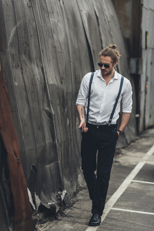 Foto de bearded stylish man in formal wear and sunglasses holding lighter and walking with hand in pocket - Imagen libre de derechos