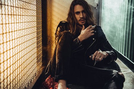 Photo pour bearded long haired man in leather jacket smoking cigarette and looking at camera - image libre de droit