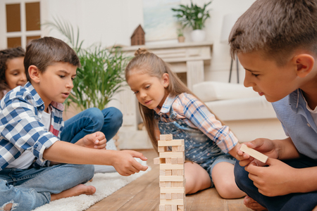 Foto de children playing blocks wood game together at home - Imagen libre de derechos