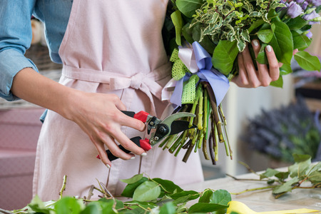Photo for young florist in apron holding bouquet and cutting green stems with secateurs - Royalty Free Image