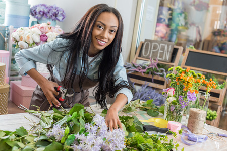 Foto de african american woman in apron holding secateurs while cutting flowers and smiling at camera in flower shop - Imagen libre de derechos
