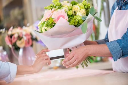 Photo pour client giving credit card to florist holding bouquet - image libre de droit
