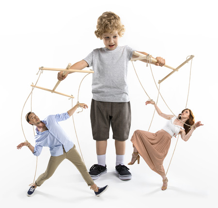 Foto de boy puppeteer controlling parents with strings isolated on white - Imagen libre de derechos
