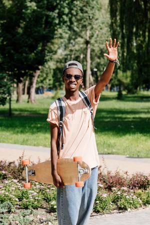 Foto de african american man with outstretched arm holding longboard - Imagen libre de derechos