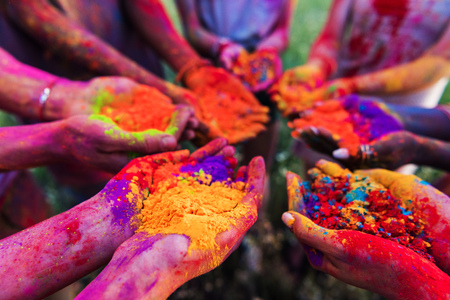 Foto de young people holding colorful powder in hands at holi festival - Imagen libre de derechos
