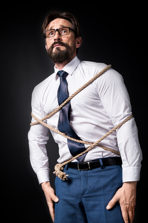 Foto de scared middle aged businessman in eyeglasses standing tied with rope - Imagen libre de derechos