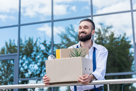 Photo pour businessman with cardboard box with office supplies in hands standing outside office building, quitting job concept - image libre de droit