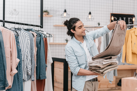 Photo for business owner holding pile of pants while working in boutique before opening - Royalty Free Image
