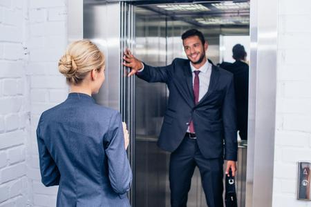 Photo pour businessman holding elevator door for woman - image libre de droit