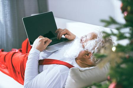Photo pour santa claus using laptop - image libre de droit