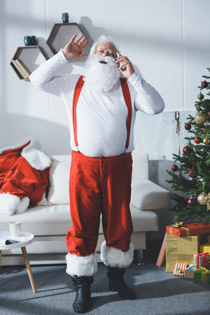 Photo pour santa claus talking on smartphone - image libre de droit