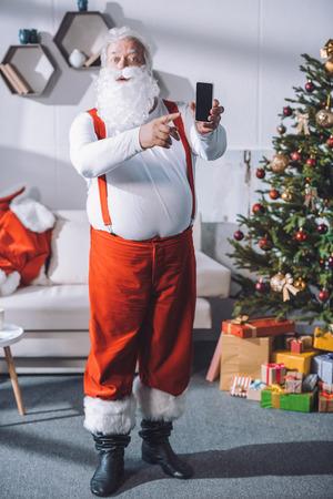 Photo pour santa claus pointing at smartphone - image libre de droit