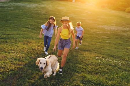 Photo pour teenagers walking with dog - image libre de droit