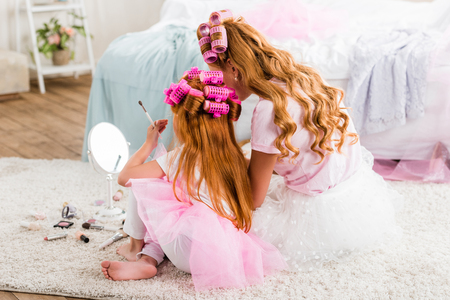 Photo for back view of mother and daughter with curlers on heads doing makeup together - Royalty Free Image