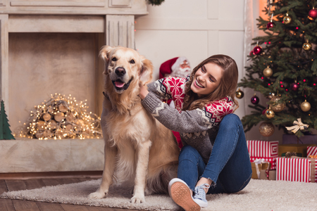 Foto de young woman and dog at christmastime - Imagen libre de derechos