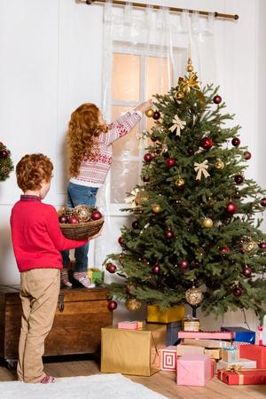 Photo pour siblings decorating christmas tree - image libre de droit
