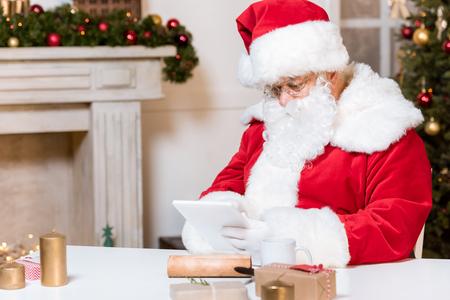 Photo pour santa claus using tablet - image libre de droit