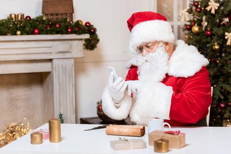 Photo pour santa claus using smartphone - image libre de droit