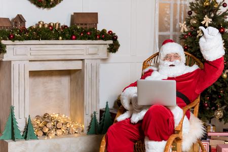 Photo pour santa claus with laptop at home - image libre de droit