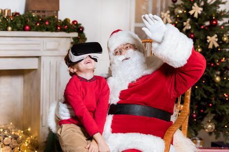 Photo pour santa claus and kid in vr headset - image libre de droit