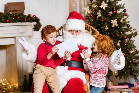 Photo pour santa claus and children with digital devices - image libre de droit