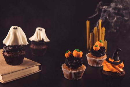 Photo for close-up view of sweet decorative halloween cupcakes, book and candles - Royalty Free Image