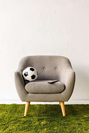 Foto de Football ball and remote controller on armchair - Imagen libre de derechos