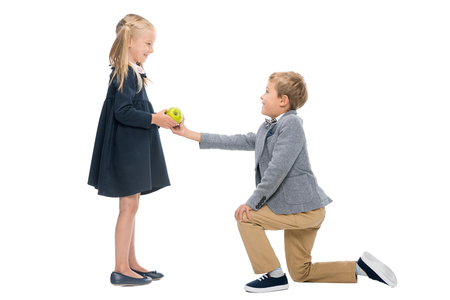 Foto de schoolboy presenting apple to girl - Imagen libre de derechos