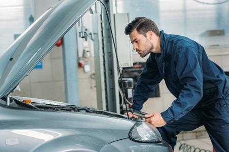 Foto de Automechanic looking under car hood - Imagen libre de derechos