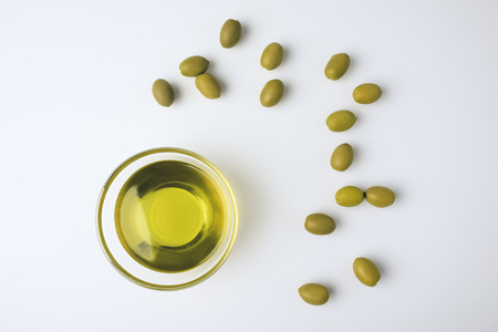 Photo pour Top view of glass bowl with olive oil and scattered green olives isolated on white   - image libre de droit