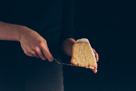 Foto de cropped view of female hands holding piece of cake,  isolated on black - Imagen libre de derechos